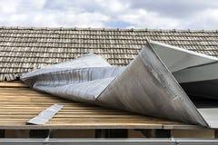 De bovenkant van het metaaldak door een sterke wind wordt vernietigd die stock afbeelding