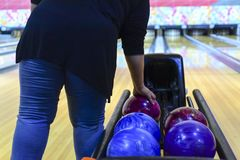 De bowlingspeler neemt de kegelenbal stock afbeelding