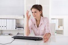 De boze en geschokte jonge vrouwenzitting in bureau het dragen nam toe stock foto's