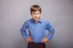 De boze handen van de tienerjongen op heupen grijze achtergrond royalty-vrije stock fotografie