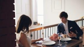 De boze jonge mens vecht met zijn verstoord meisje tijdens romantische datum in aardig restaurant De kerel spreekt dan stock video
