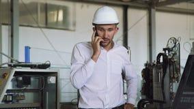 De boze manager die en op de telefoon in de fabriek 4K spreken schreeuwen stock footage
