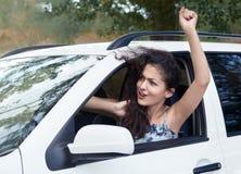 De boze meisjesbestuurder binnen auto, onderzoekt de afstand, heeft emoties en golven, zomer Stock Fotografie