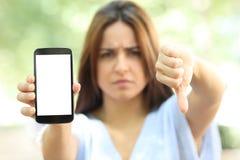 De boze vrouw toont telefoon het lege scherm in de straat stock afbeeldingen