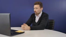 De boze werkgever bedreigt de partners met een houten bijl tijdens videoconferentie stock videobeelden