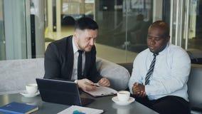 De boze zakenman in zwart pak kritiseert streng zijn Afrikaanse Amerikaanse werknemer tijdens vergadering in moderne koffie stock video
