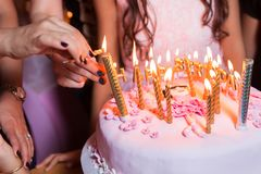De bränner stearinljus på födelsedagen Stearinljus för belysning för hand för moder` s i födelsedagkaka Arkivfoton