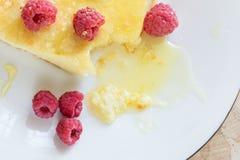 De braadpan van de close-upkaas met frambozen motregende met honing op witte plaat stock afbeelding