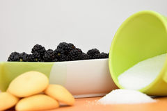De braambessen in een ceramische kom, koekjes en een kop van suiker morsen Stock Fotografie