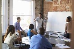 De Brainstormingsvergadering van zakenmanat whiteboard in stock foto's