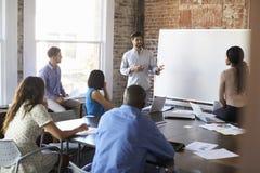 De Brainstormingsvergadering van zakenmanat whiteboard in royalty-vrije stock afbeelding