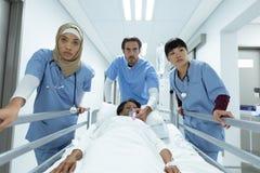 De brancardbed van de medisch team duwend noodsituatie in gang stock afbeeldingen
