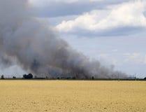 De brand is ergens voorbij het geploegde gebied Donkere rook van een brand Royalty-vrije Stock Afbeelding