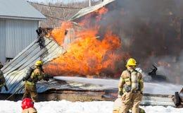 De brand van het eilandbouwbedrijf De brandbestrijders vechten opvlammende schuur Stock Foto