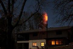 De Brand van de huisschoorsteen bij Nacht met het Branden van Sintels die aan Dak vallen Stock Foto