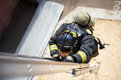 De brandbestrijder beklimt op brandtreden Stock Afbeelding