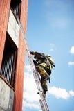 De brandbestrijder beklimt op brandtreden Stock Foto's