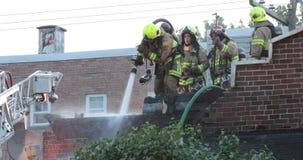 De brandbestrijder bespuit water op muur stock videobeelden