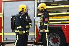 De brandbestrijder in de ademhaling van toestel wordt geïnformeerd Stock Fotografie