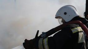 De brandbestrijder dooft brand met een waterstraal stock videobeelden