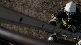 De brandbestrijder in gasmasker neemt hoog op de ladder toe stock footage