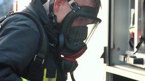 De brandbestrijder kleedde zich in eenvormig en een zuurstofmasker E stock videobeelden