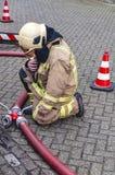 De brandbestrijder zit op de grond stock fotografie