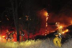 De brandbestrijders aan het werk in het midden van een weide vlammen op stock fotografie