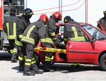 de brandbestrijders in actie en trekken verwond Stock Fotografie