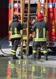De brandbestrijders in actie nemen de houten ladder Stock Fotografie