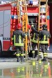 De brandbestrijders in actie nemen de ladder Stock Foto