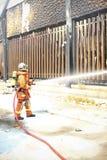 De brandbestrijders bespuiten water aan wildfire Stock Foto's