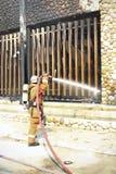 De brandbestrijders bespuiten water aan wildfire Stock Afbeelding