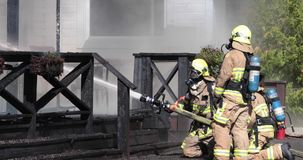 De brandbestrijders bespuiten water op muur met slang in daglichtvoorwaarde stock videobeelden