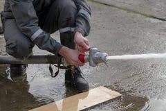 De brandbestrijders bespuiten water tijdens een opleidingsoefening stock foto
