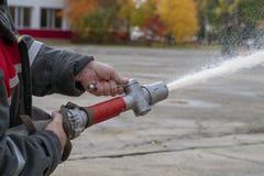 De brandbestrijders bespuiten water tijdens een opleidingsoefening stock afbeelding