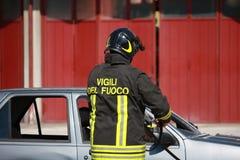 De brandbestrijders bevrijdden een gewonde in auto na een acci wordt opgesloten die Royalty-vrije Stock Foto's