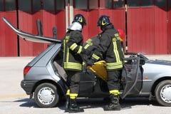 De brandbestrijders bevrijdden een gewonde in auto na een acci wordt opgesloten die Stock Afbeelding