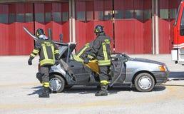De brandbestrijders bevrijdden een gewonde in auto na een acci wordt opgesloten die Stock Fotografie