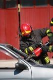 De brandbestrijders bevrijdden een gewonde in auto na een verkeersacci die wordt opgesloten Stock Foto's