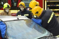 De brandbestrijders bij een auto verpletteren Royalty-vrije Stock Foto