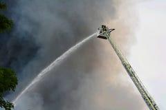 De brandbestrijders bij huis steken in brand Stock Foto