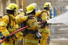 De brandbestrijders die, voorgrond is daling van wateraanzetsteen, Sel opleiden stock afbeeldingen