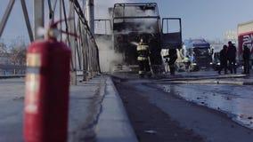 De brandbestrijders doven een vrachtwagen op rijweg stock videobeelden