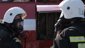De brandbestrijders dragen gasmaskers en uniformen terwijl stock videobeelden