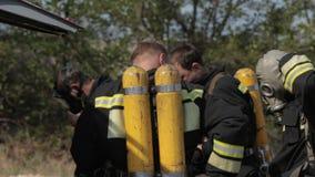 De brandbestrijders dragen maskers en ballons stock videobeelden