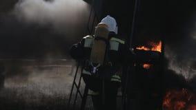 De brandbestrijders dragen uniformen dichtbij brandvrachtwagen en looppas stock videobeelden