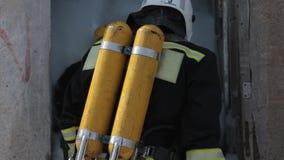 De brandbestrijders in eenvormig en gasmaskers openen stock video