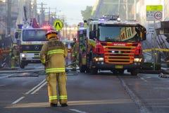 De brandbestrijders en de reddingsbemanning wonen winkelontploffing bij Stock Foto's