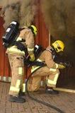 De brandbestrijders gaan een rook gevuld gebouw in stock afbeeldingen